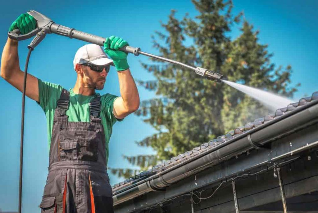 man-using-pressure-washer-to-clean-roof-and-gutters_orig